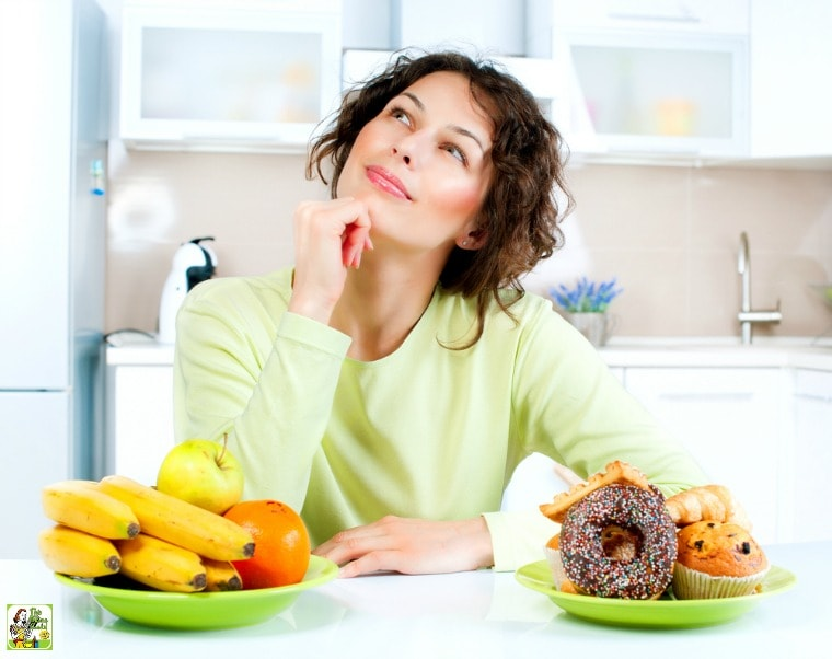 Young woman thinking with green plates of fruit and donuts and pastries in a white kitchen