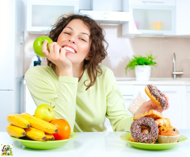 Young woman with healthy fruit and donuts and pastries in a white kitchen.