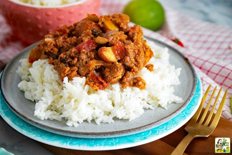 A plate of Mexican Picadillo on white rice with fork, napkin, and lime.