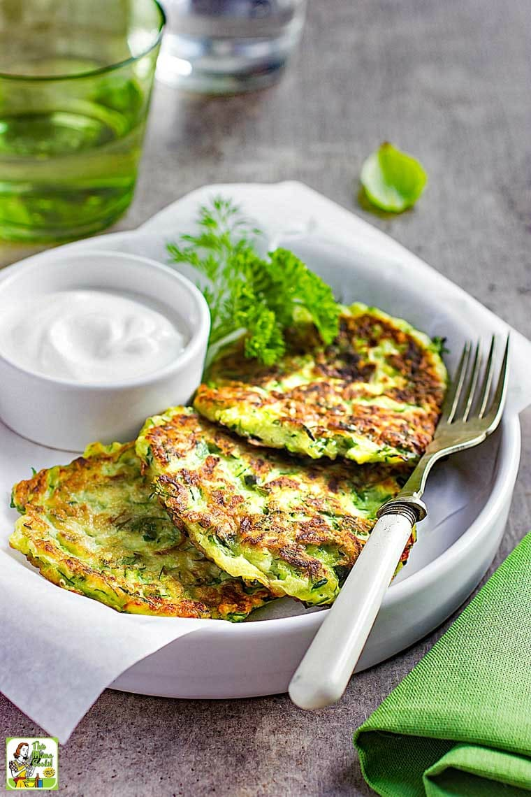 Plate of Zucchini Fritters with bowl of sour cream and a fork