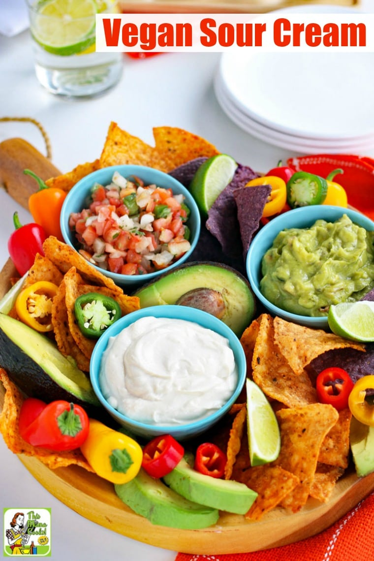 A platter with a small blue bowl of Vegan Sour Cream with slices of limes, tortilla chips, mini sweet peppers, avocados, blue bowls of salsa and guacamole, and white plates.