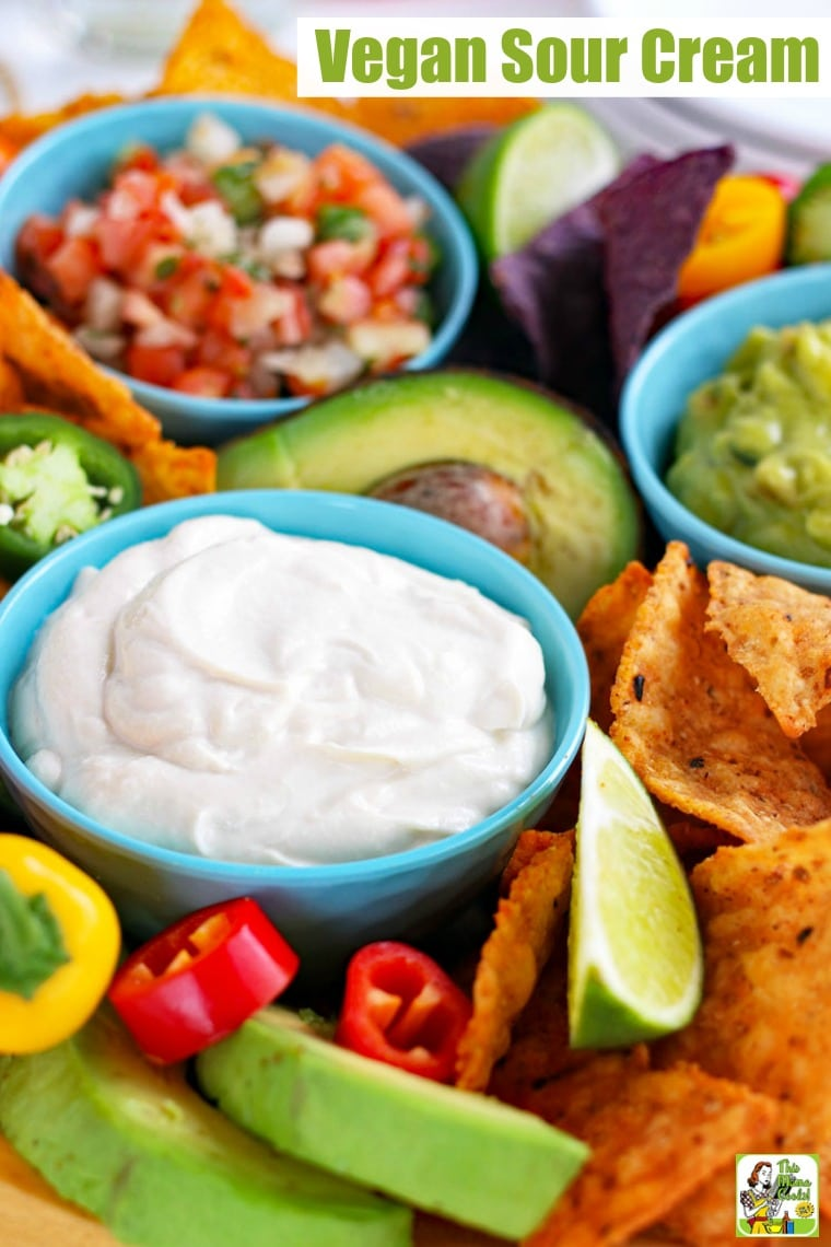 Closeup of blue bowls of creamy vegan sour cream, salsa, and guacamole with slices of lime, tortilla chips, sweet peppers, and avocados.