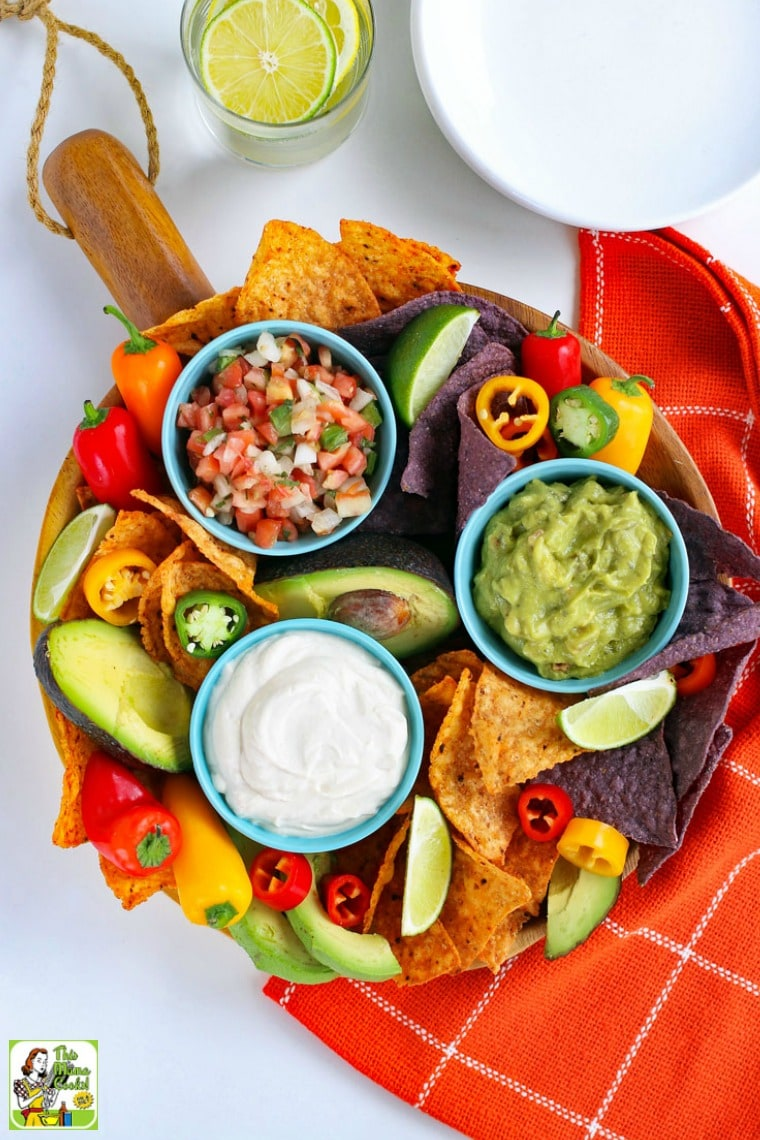 Overhead view of a platter with a bowls of Vegan Sour Cream, salsa, and guacamole with dippers of sweet peppers and tortilla chips along with big bowls of vegan sour cream and a water glass.