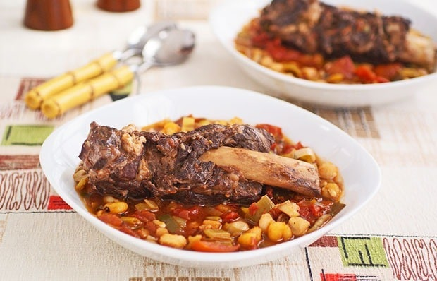 A bowl of braised short ribs on a colorful tablecloth with another bowl and spoons in the background.