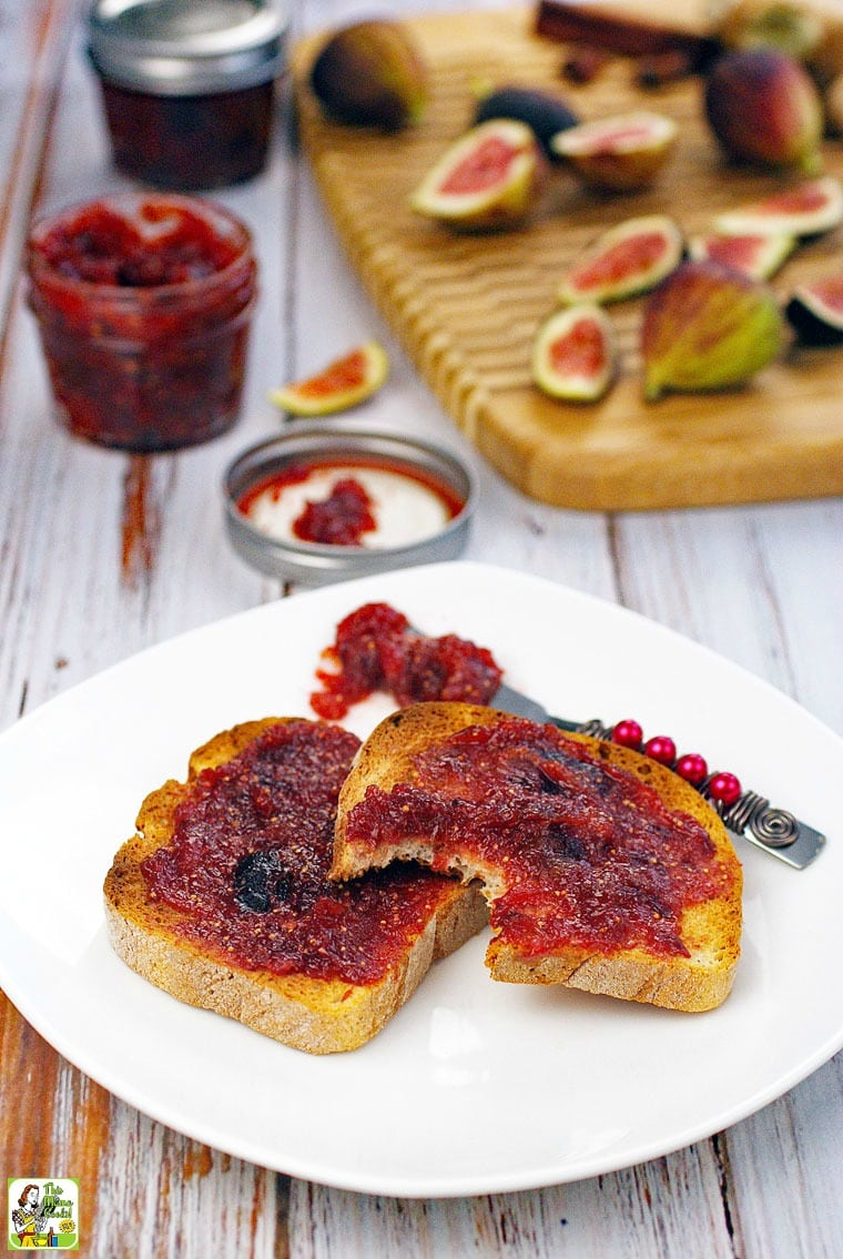 Toast with fig jam on a plate with a jar of fig jam and figs in the background.