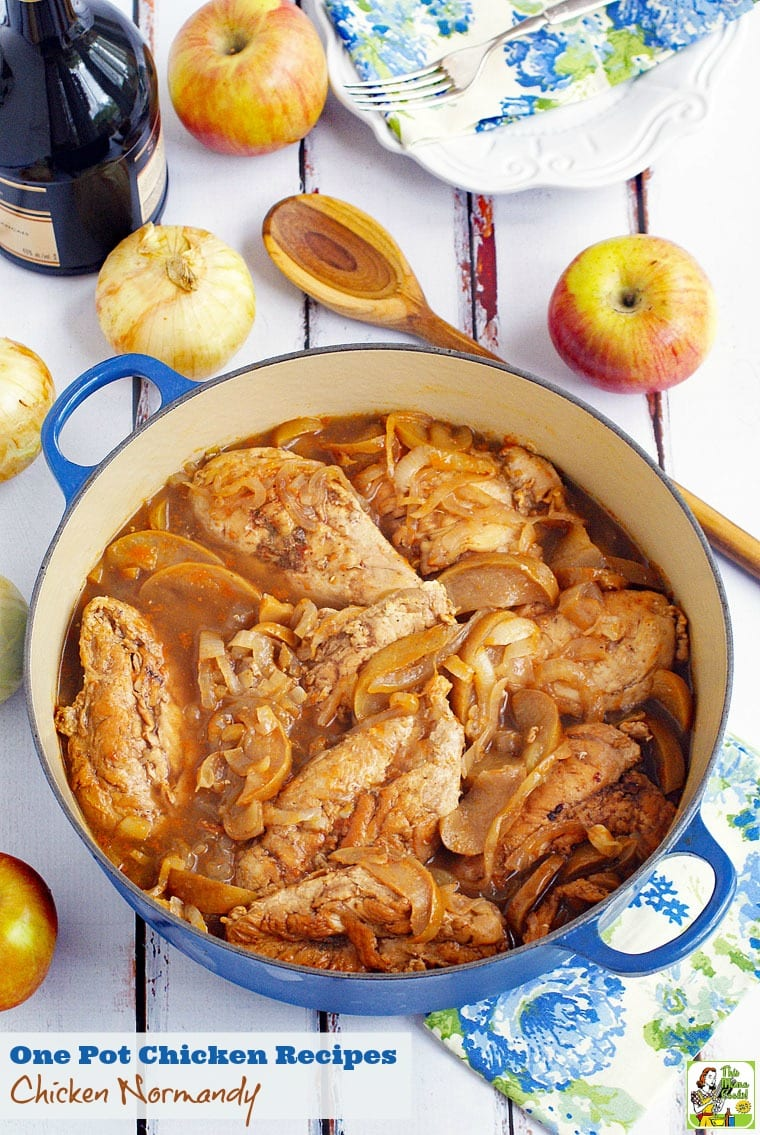 A pot of chicken Normandy made with apples and onions. With apples, onions, a bottle of brandy, floral napkins and a wooden serving spoon.