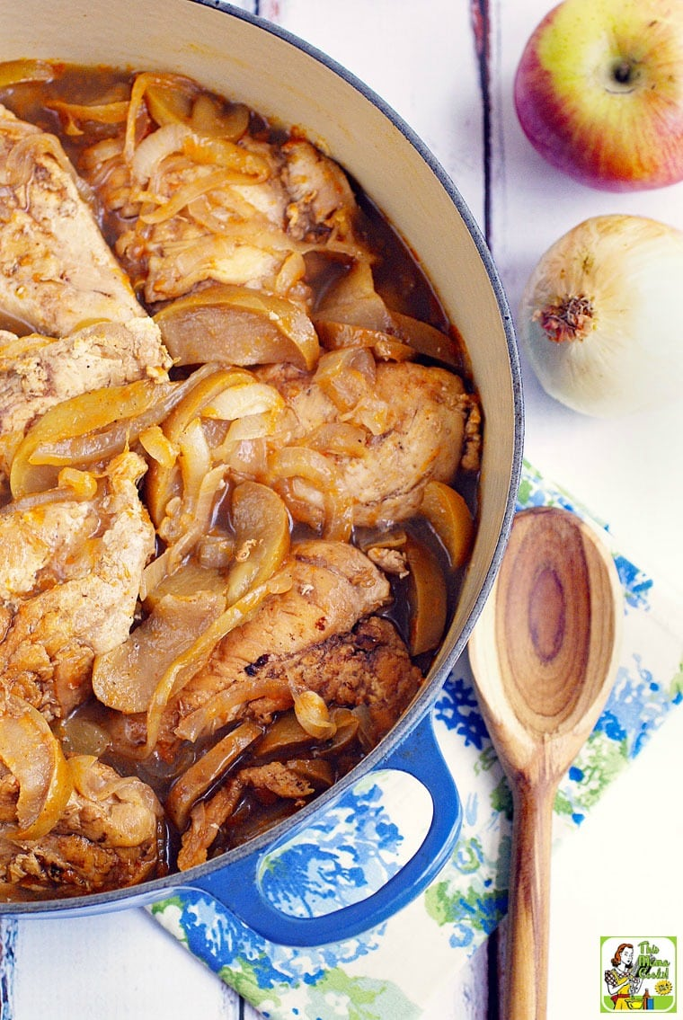 A blue Dutch oven filled with chicken and onion stew with a wooden serving spoon and floral napkin.