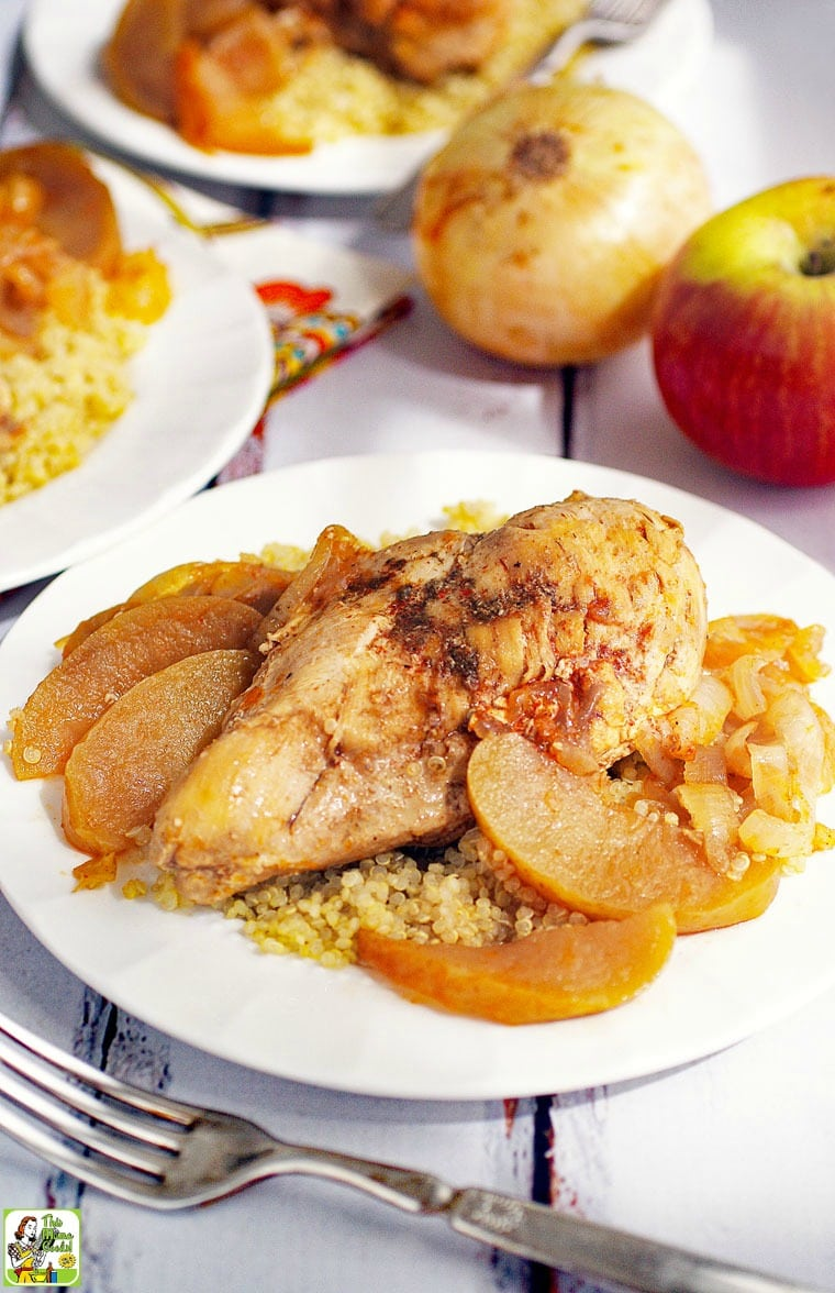 Plate of Chicken Normandy with apples and onions served on quinoa with fork.