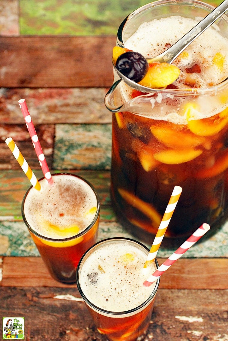 A pitcher and glasses with straws of iced tea sangria with fruit.