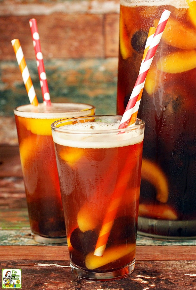 A pitcher and two glasses of iced tea sangria with striped straws.