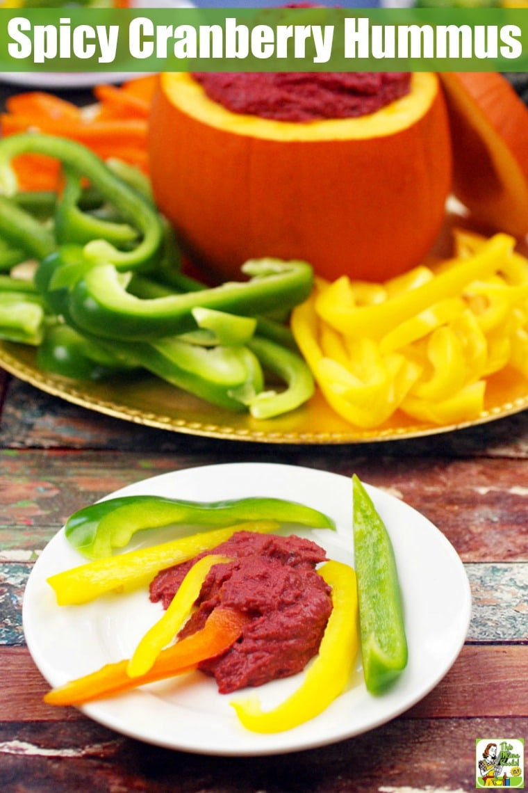 A white appetizer plate of sliced peppers and hummus and a large serving platter of peppers and Cranberry Hummus in a small pumpkin