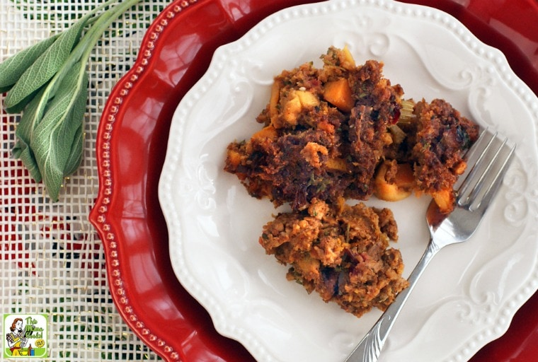 Gluten Free Cornbread Stuffing Recipe with Chorizo, Squash & Apples on a white and red plates with fork and a sprig of sage.