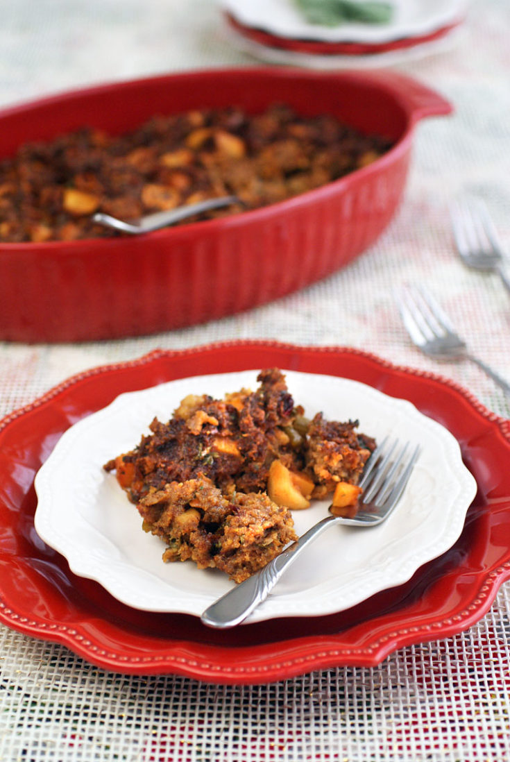 A holiday plate and casserole dish of Gluten Free Cornbread Stuffing with Chorizo, Squash & Apples.
