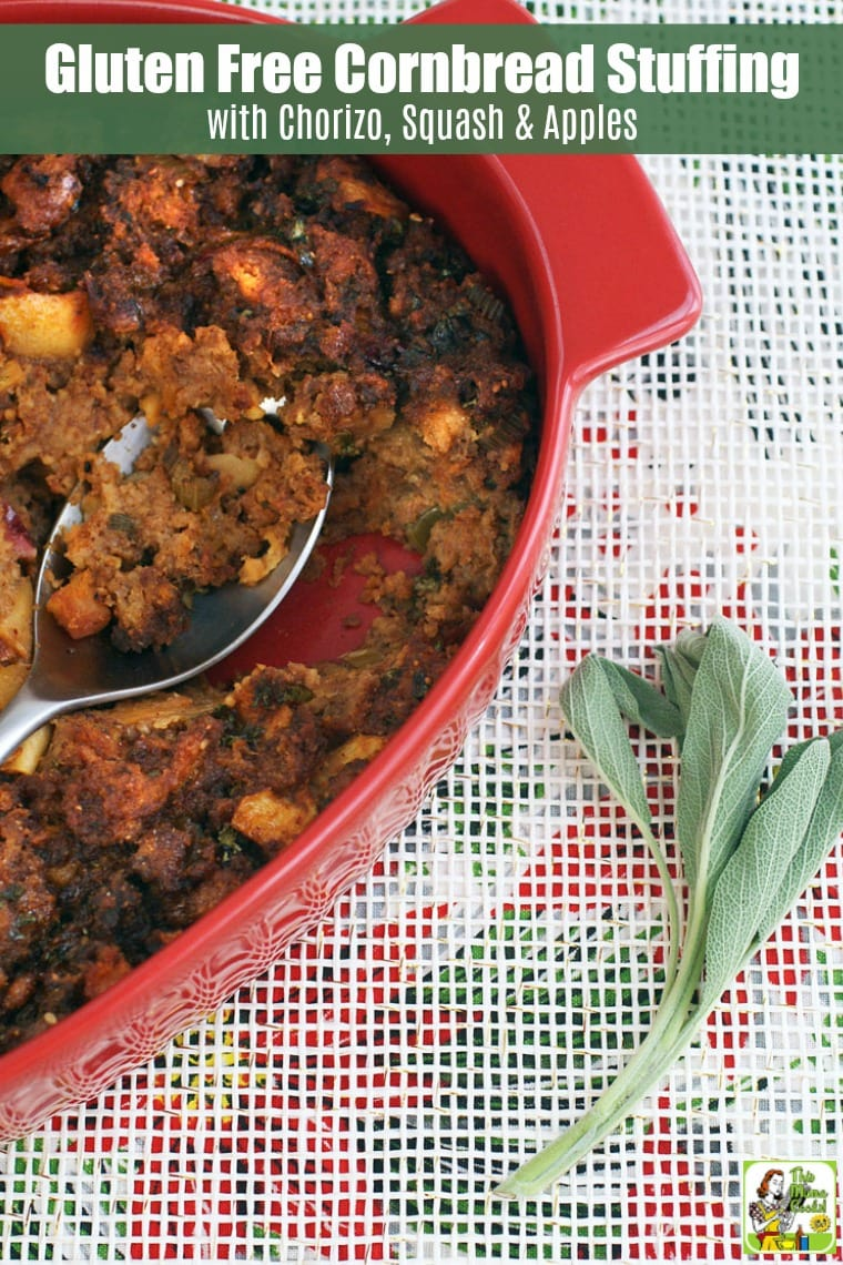 A red casserole dish of cornbread stuffing with chorizo, squash and apples with a sage sprig on a white background.