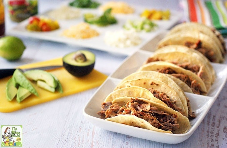 A platter of Slow Cooker Pulled Pork Tacos with avocados, limes and other topping