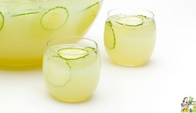 Two glasses and a punch bowl of sparkling green sangria filled with slices of cucumber and grapes.