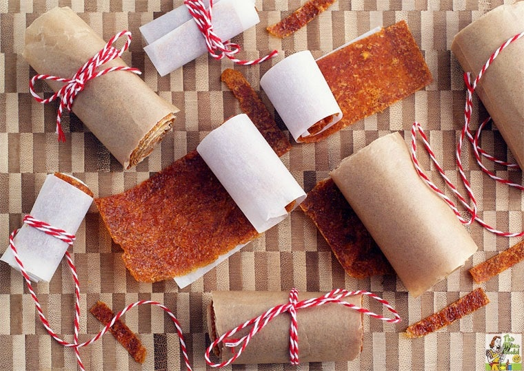 Rolls of Orange Fruit Leather tied in kitchen twine on a wooden cutting board.