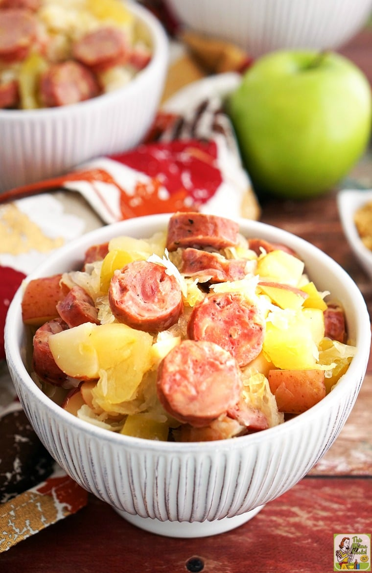 Slow Cooker Sauerkraut and Sausage with Apples and Potatoes in a white bowl.
