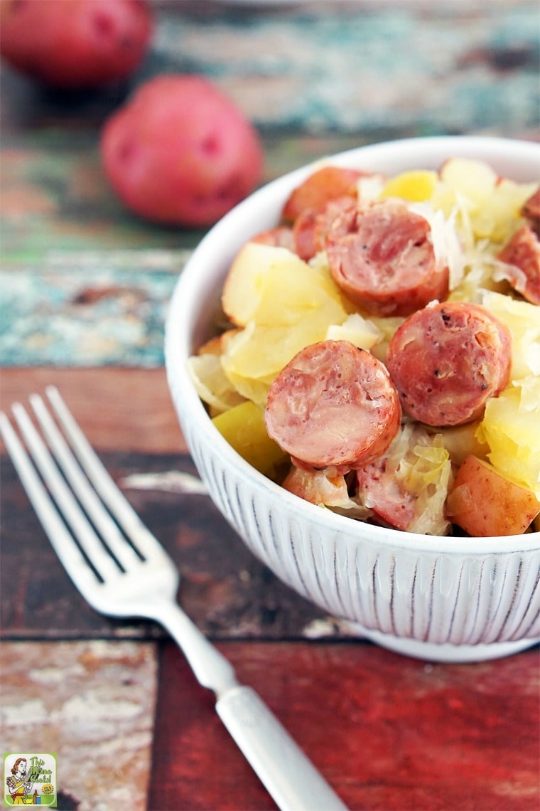 A closeup of slow cooker sauerkraut and sausage with apples and potatoes in a white bowl with fork and red potatoes.