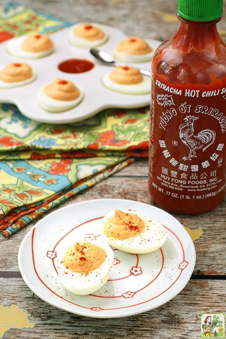 Two Sriracha Deviled Eggs on a white plate with a bottle of sriracha sauce in the background.