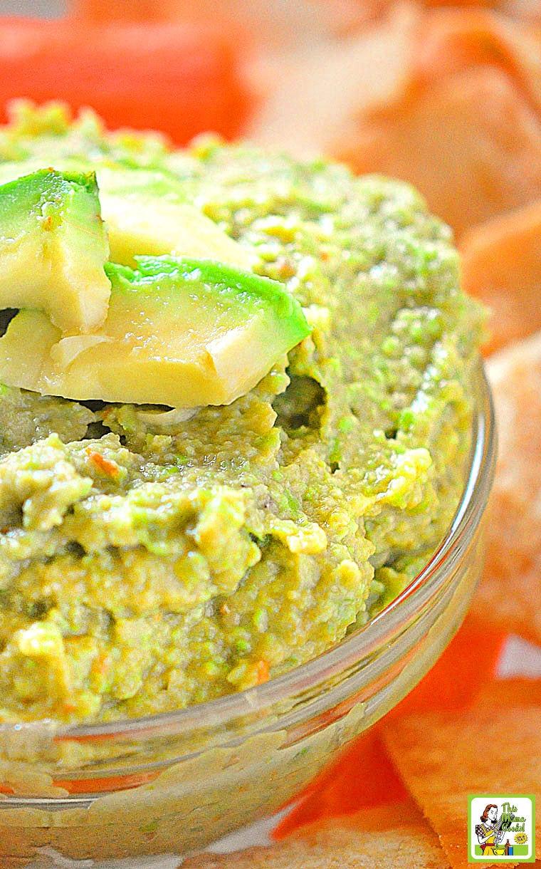 Edamame Avocado Dip in a glass bowl with a slice of avocado.