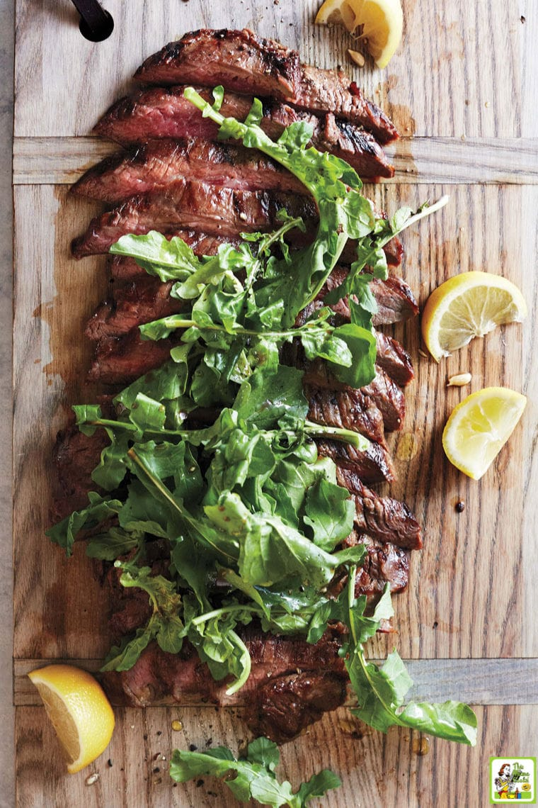 Sliced grillied flank steak with arugula on a wooden cutting board with lemon slices.