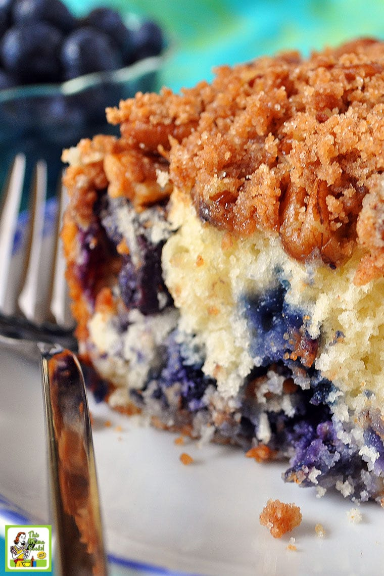 A slice of Blueberry Muffin Streusel Cake on a white plate with fork with fresh blueberries in the background.