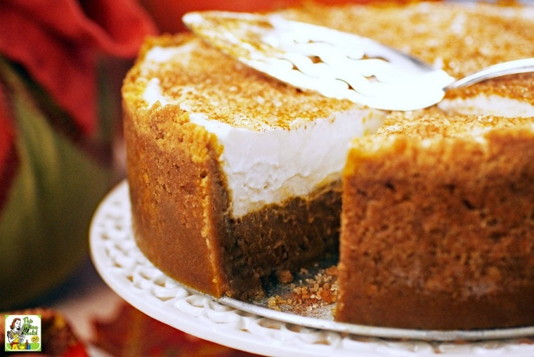 Gluten Free Dairy Free Pumpkin Pie with a slice missing with a serving knife on a white cake stand.
