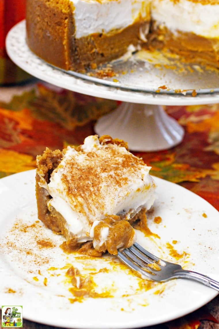 A slice of pumpkin pie with fork and a cake stand in the background.