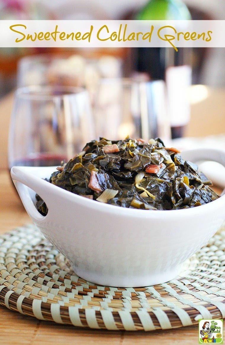 Closeup of a white bowl of sweet collard greens on a woven mat with wine glasses in the background.