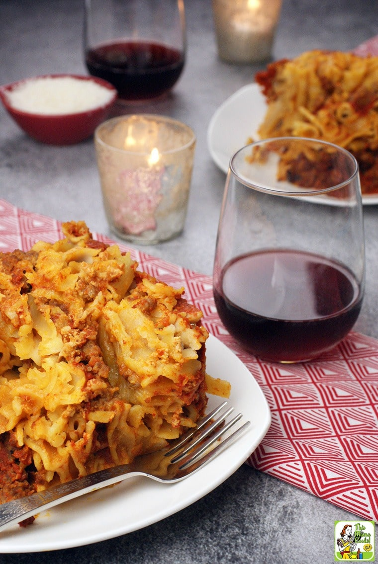 A plate of Crock-Pot Baked Ziti on a white plate with silver fork with a red napkin with a glass of red wine with a candle, another plate of ziti, and a small bowl of shredded cheese.