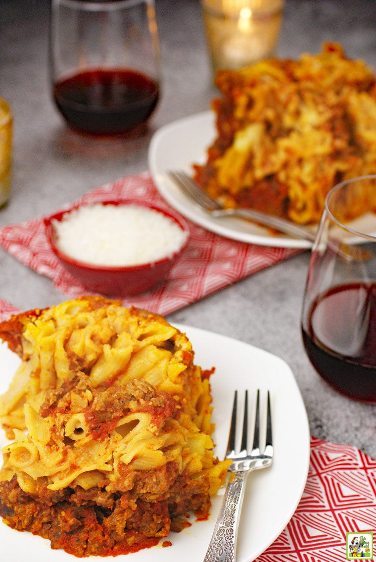 Plates of gluten free baked ziti on white plates with forks, red napkins, a small red bowl of shredded cheese, and glasses of red wine.