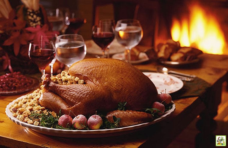 A whole smoked turkey with stuffing and potatoes on a platter on a table with wine glasses and meal side dishes.