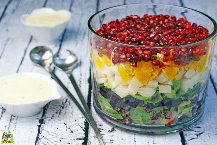A layered Mexican Christmas Salad in a glass trifle bowl