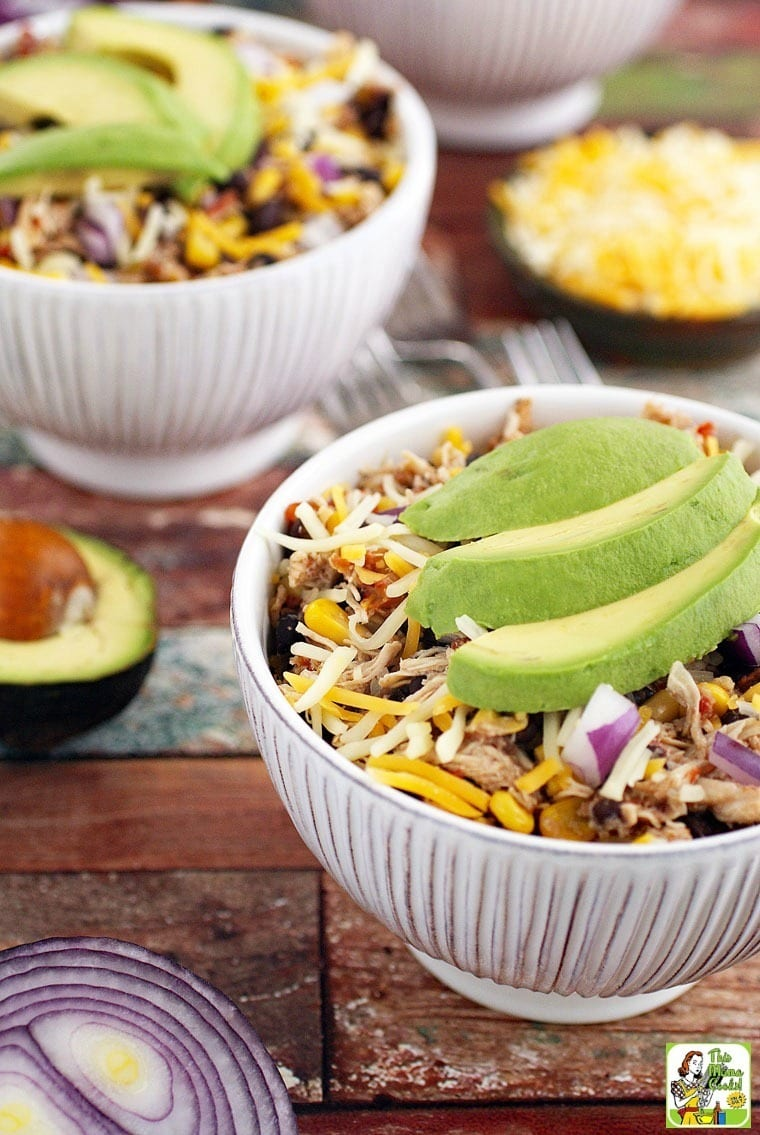 White bowls of Mexican Shredded Chicken Recipe with Black Beans & Corn with slices of avocado and diced onion