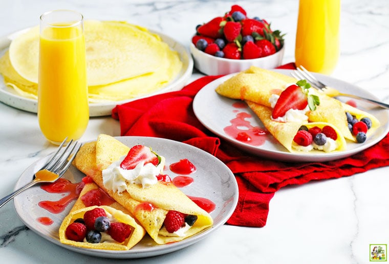 Plates of rice flour crepes with raspberries, blueberries, whipped cream, and berry drizzle with red napkins and glasses of orange juice.