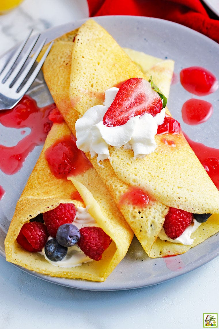 Closeup of two crepes on a plate stuffed with berries and whipped cream.