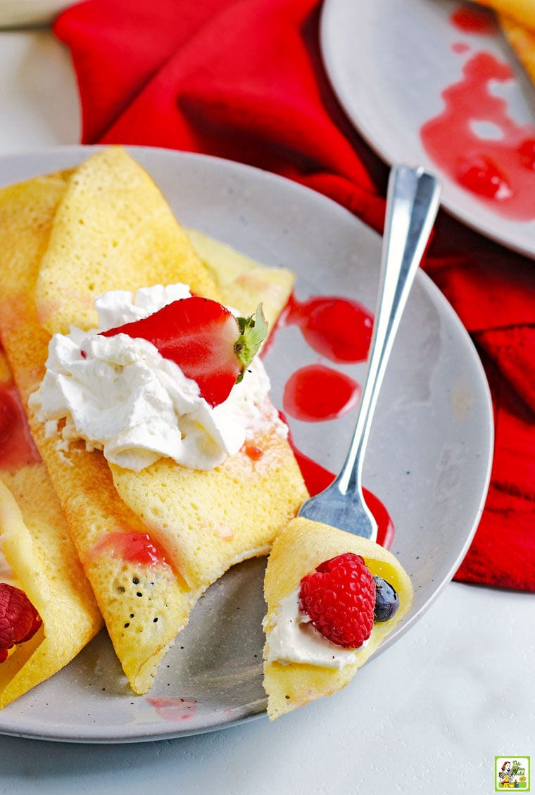 A forkful of piece of crepe with raspberry on a plate of crepes, berries, and whipped creme.