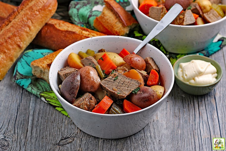 Slow Cooker Venison Stew in a white bowl with a spoon next to a small bowl of horseradish and rolls of crunchy bread.
