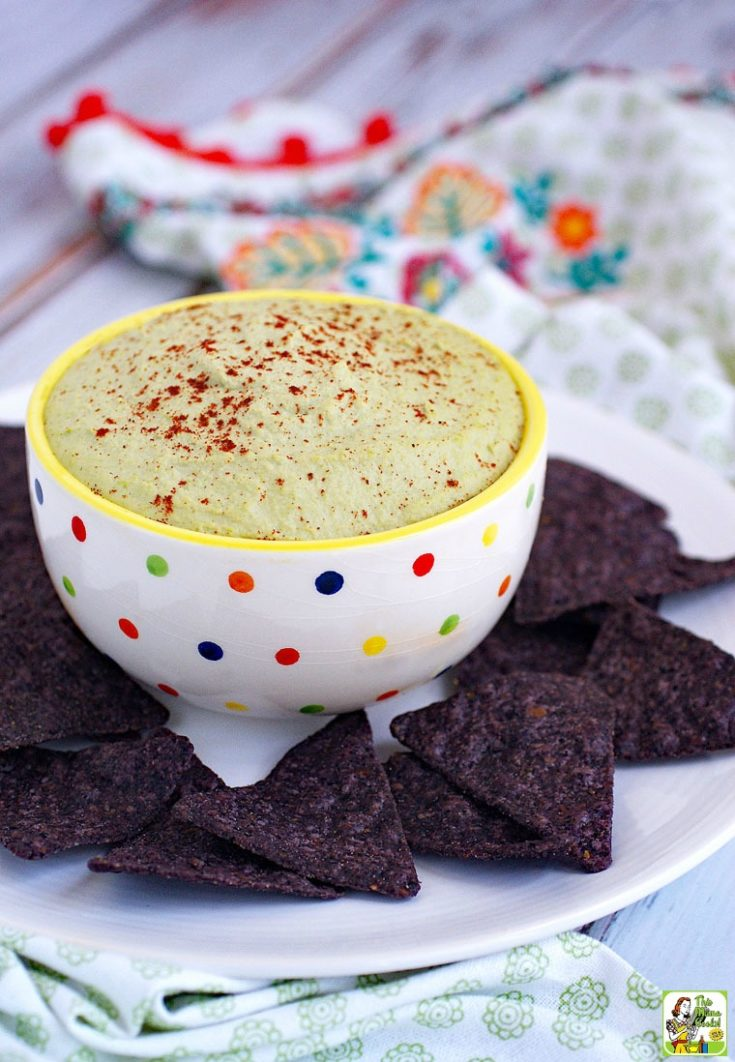 A white bowl with polka dots with green edamame hummus on a white dish with blue tortilla chips.