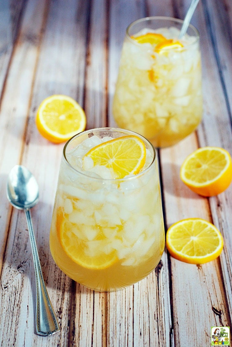 Two cocktail glasses of Meyer Lemon Shrub Drinks on Ice with sliced lemons and spoon.