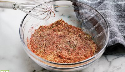 A glass bowl of Homemade Taco Seasoning Mix with a wire whisk and gray dish towel.