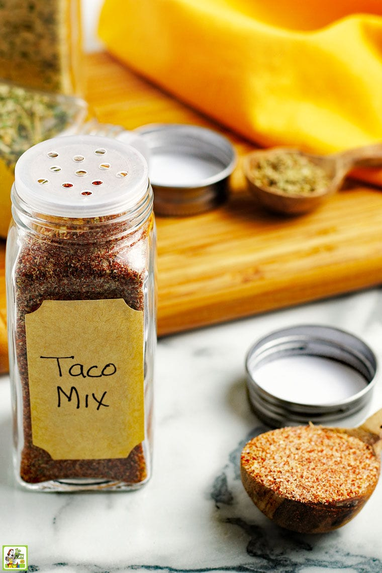 Jars of Taco Seasoning Mix, a measuring spoon of taco mix, and a wooden cutting board on a marble counter top with a yellow napkin in the background.