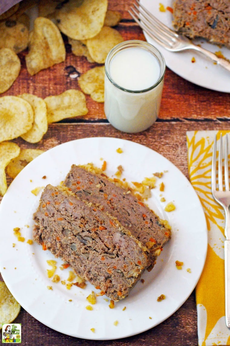 Meatloaf with Potato Chips & Carrots on a white plate with a glass of milk, a fork and napkin, and extra potato chips