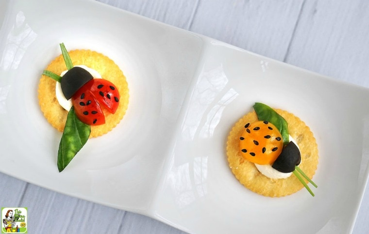 Tomato and cheese ladybugs snack cracker appetizers on a white dish.