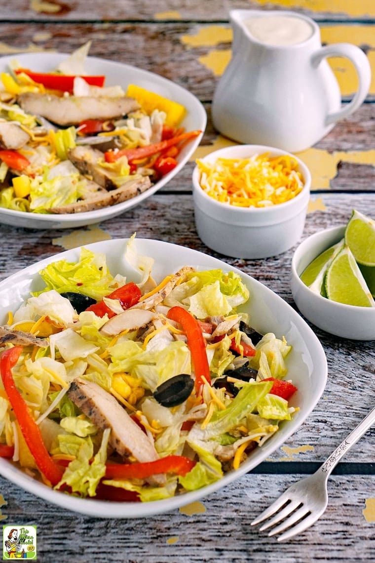 Two bowls of Chicken Fajita Salad with a pitcher of salad dressing.