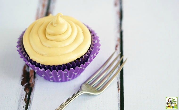 A closeup of a Chocolate Cupcake with Dulce de Leche Frosting with a colorful cupcake liner and an antique silver fork