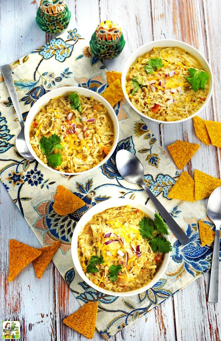 Bowls of Slow Cooker Creamy Verde Chicken Chili with chips and serving spoons.