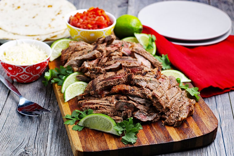 Sliced carne asada meat with limes and cilantro on a wooden cutting board with taco fixings in the background.
