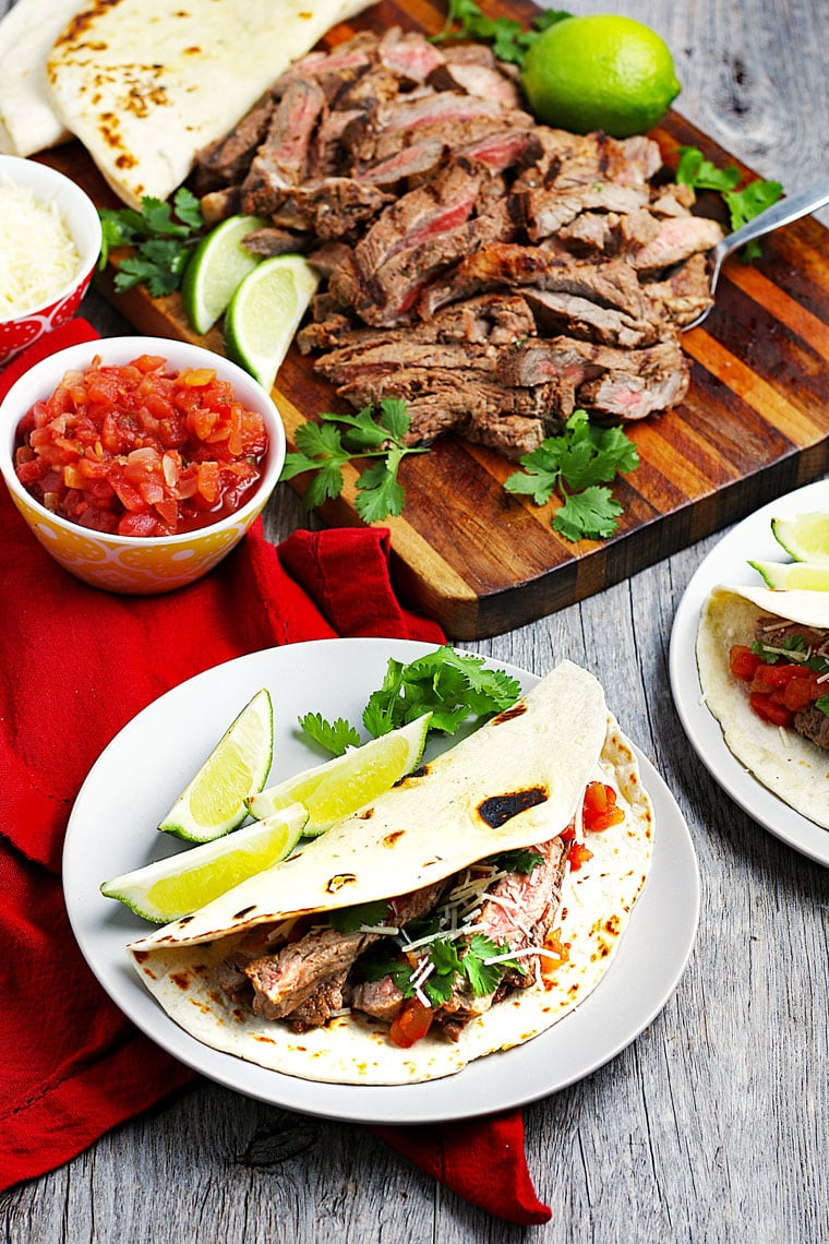 Overhead shot of carne asada tacos on white plates and sliced carne asada meat with limes and cilantro on a wooden cutting board and a bowl of salsa.